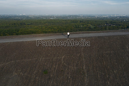 businessman standing on hill against sky