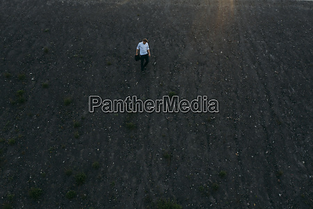 businessman moving downhill during sunset