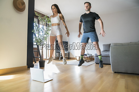 couple jumping while exercising on hardwood