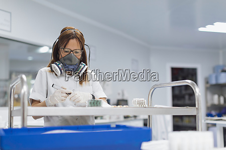 confident mature female technician holding marker