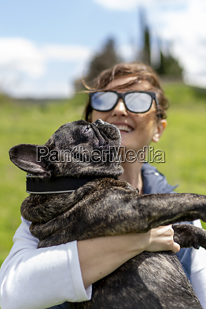 happy woman carrying her lazy bulldog