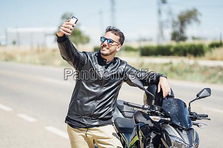 biker with motorbike taking a selfie