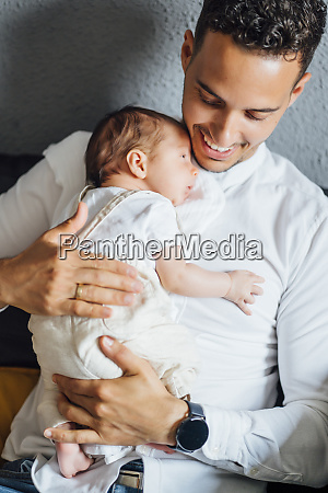 happy father carrying baby boy at