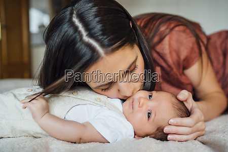loving mother kissing baby boy in