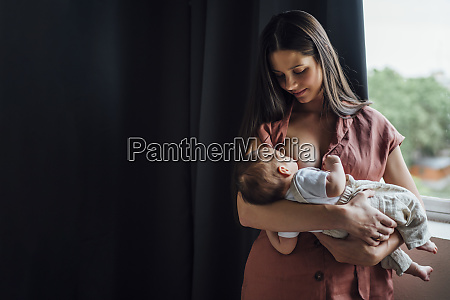 mother breastfeeding baby boy while standing