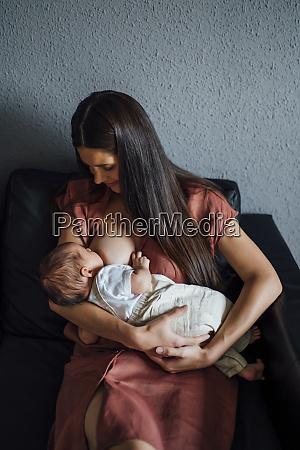 mother breastfeeding baby boy while sitting