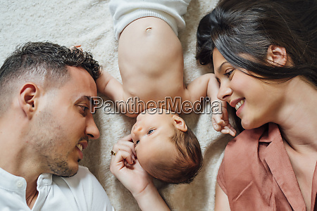 loving parents lying with baby boy