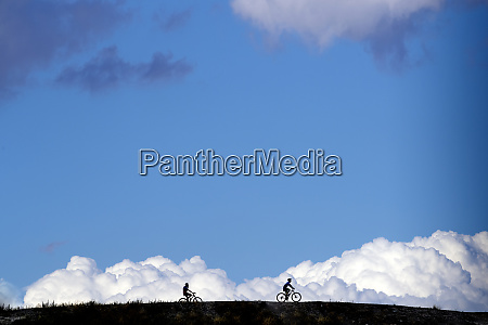 silhouette cyclists riding bicycles on field
