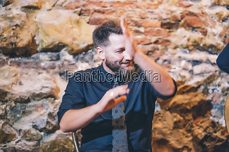 bearded smiling singer clapping hands while