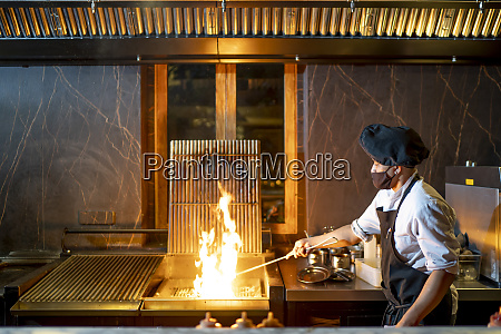 chef wearing protective face mask preparing
