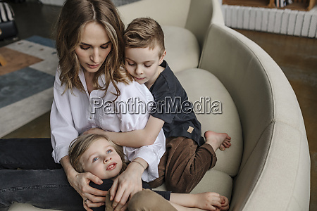 blond woman sitting with sons on