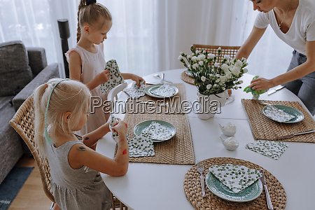 mother with daughters setting dining table
