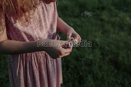 girls hands holding daisy flowers