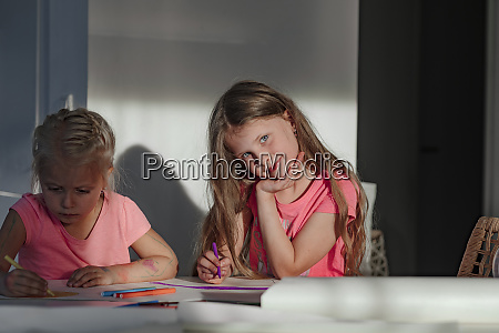 happy girl sitting with sister coloring