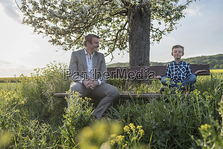 smiling man looking at son practicing