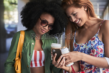girlfriends with coffee to go using