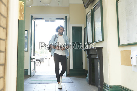 young trendy man entering railroad station
