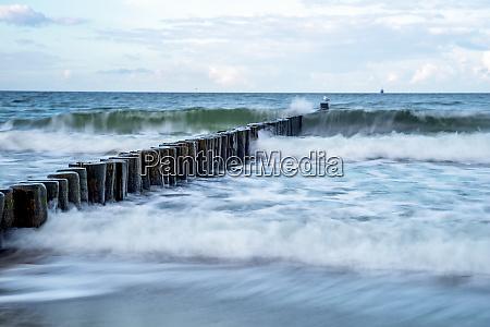 waves smashing against coastal groyne at