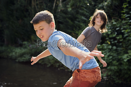 boys playing in stream at forest