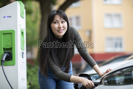 carsharing woman charging an electric car