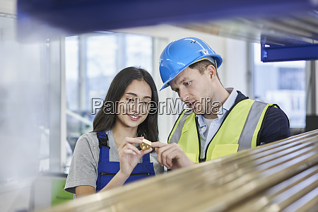 female worker and supervisor examining metallic