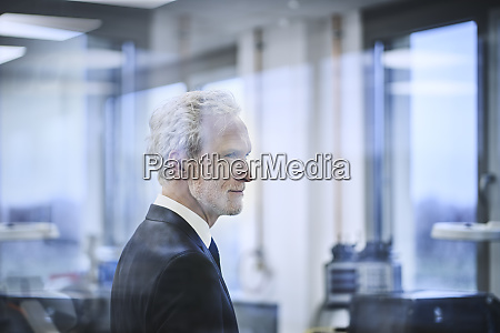 thoughtful male manager behind glass in