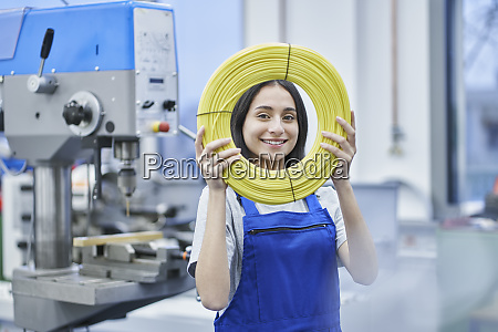 happy female worker looking through rolled
