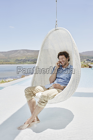 man sitting in hanging chair above