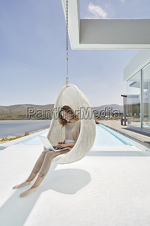 woman sitting in hanging chair above