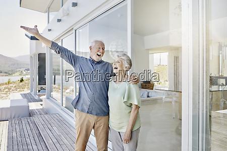 carefree senior couple standing at luxury