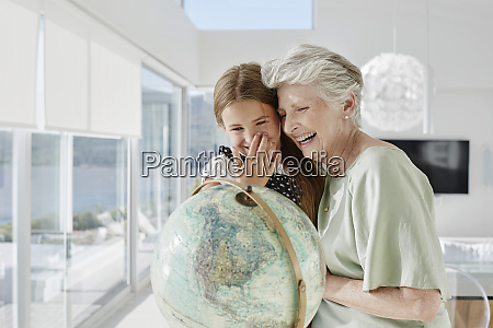 laughing grandmother and granddaughter with globe