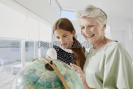 grandmother and granddaughter looking at globe