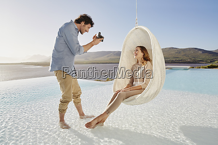 man taking picture of woman sitting