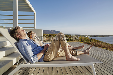 couple lying on deck chairs at