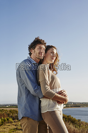 affectionate couple hugging at the sea