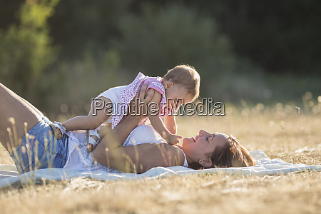 happy woman carrying baby girl while