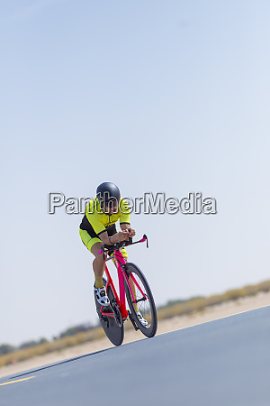 determined cyclist riding bicycle on road