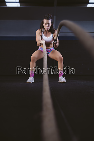 young woman exercising with battle ropes