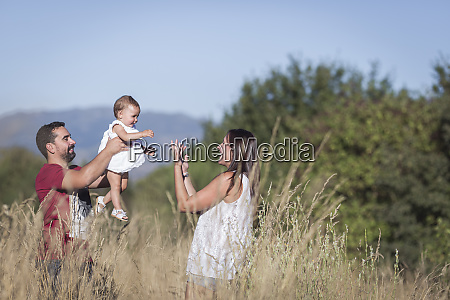 happy family amidst plants in forest