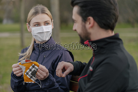 young woman giving face mask to