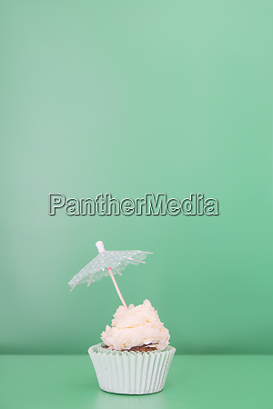 single cupcake decorated with drink umbrella