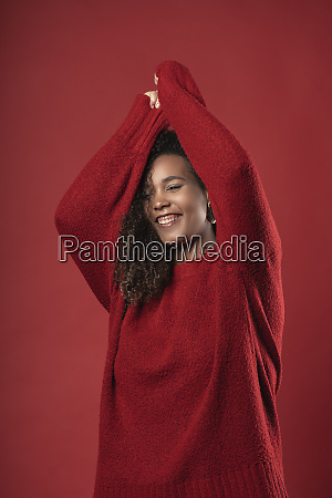 smiling young woman with arms raised