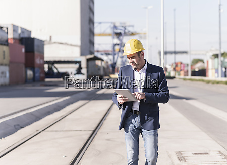 businessman wearing safety helmet using digital