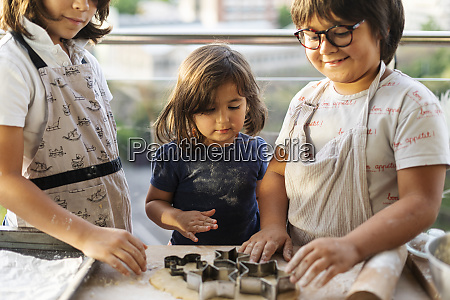 three children cutting out cookies