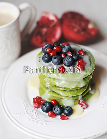 spinach pancakes with blueberries and pomegranate