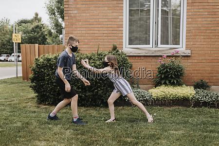 carefree siblings wearing masks playing in
