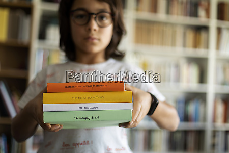 boy holding stack of four books