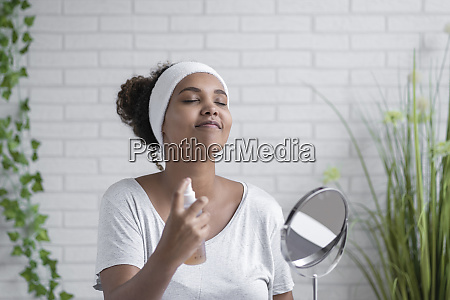 young woman with eyes closed spraying