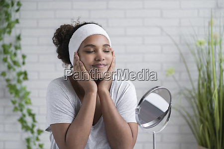 woman with eyes closed applying cleansing