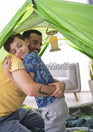 father embracing his son in tent